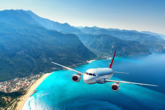 Airplane is flying over amazing mountains with forest and sea at sunrise in summer. Landscape with white passenger airplane, sky, islands and blue water. Passenger aircraft. Travel and resort. Tourism
