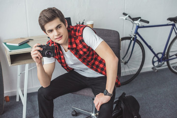 teenager with film camera sitting at home with bicycle behind