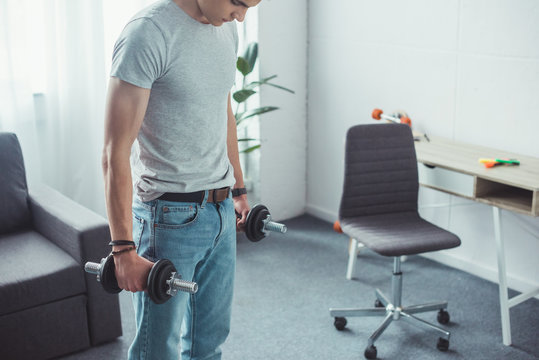 young boy training with dumbbells at home