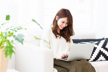 部屋でラップトップコンピュータを見る女性
