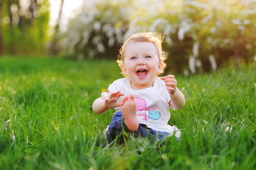 A funny baby girl is playing and smiling at the bright green grass in the park in the summer.