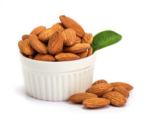 the fresh almonds in white cup on white background