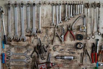 Wrench in various sizes hanging on wood background, Tool shelf against a table and wall