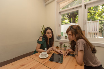 Two asian girls use a tablet while sitting in a cafe and drinking coffee.