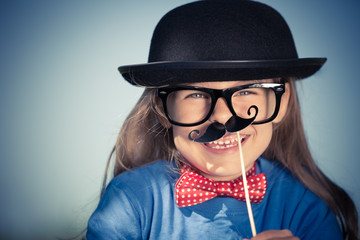 Outdoor portrait of funny happy little girl in bow tie and bowler hat. Retro stile.