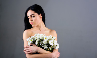 Woman hiding her breasts, covers with bouquet. Picture of woman holds bunch of lovely chamomile flowers, grey background. Cancer of breast concept. Lady covers breasts with flowers, grey background.