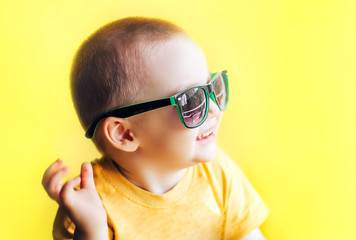 baby boy in sunglasses on yellow background