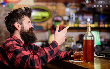 Poster Bar Hipster with beard ordered full bottle of alcohol. Relaxation concept. Man drinks whiskey or cognac. Man with happy face sits near bar counter. Guy spend leisure in bar, defocused background.