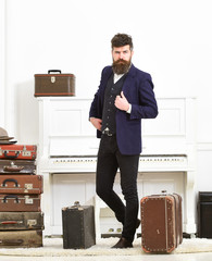 Man, traveller with beard and mustache with luggage, luxury white interior background. Macho elegant on strict face standing near pile of vintage suitcase. Luggage and travelling concept.