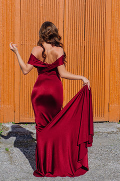Beautiful young woman in a long red evening gown with a train