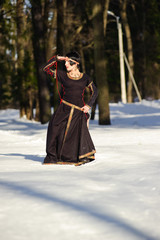 girl in a medieval dress among the snow