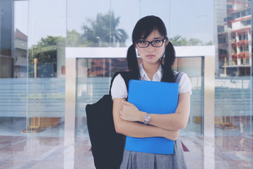 Cranky asian female student in front of university