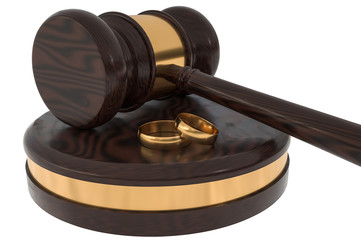 Divorce concept with wooden gavel and gold wedding rings