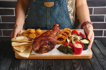 Hands holding plate with fried turkey thigh, grilled vegetables and snack for beer