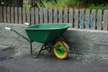 Garden Wheelbarrow Empty in the Garden. Florist work Process over Wooden Fense.