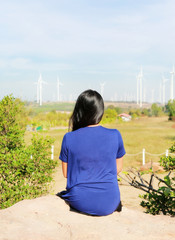 Rear view of Asian woman against wind turbine field.