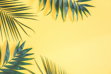 Tropical palm leaves on yellow background. Summer concept. Flat lay, top view, copy space Wall mural