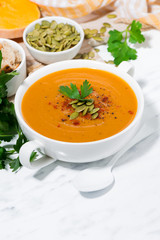 fresh soup of pumpkin and lentils on white background, vertical