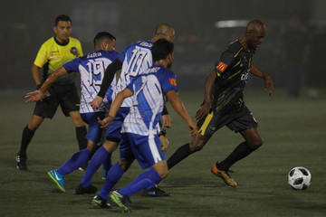 Former Salvadorean soccer players Roberto Garcia, Alex Erazo and Wilber Garcia plays ball with former French soccer player Eric Abidal during an exhibition match at Las Delicias Stadium in Santa Tecla