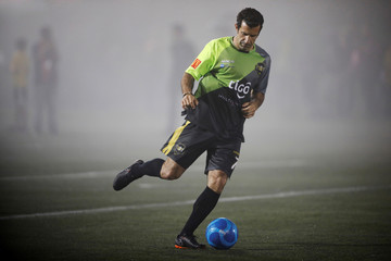 Former Portuguese soccer player Luis Figo warms up prior to an exhibition match at Las Delicias Stadium in Santa Tecla