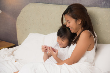 Mother with her little baby having fun in the bed. Daughter play phone.