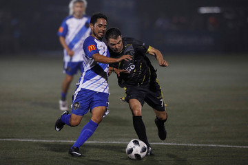 Former Salvadorean soccer player Roberto Garcia plays ball with former Argentine soccer player Javier Saviola during an exhibition match at Las Delicias Stadium in Santa Tecla