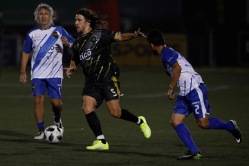 """Former Spanish soccer player Carles Puyol plays ball with former Salvadorean soccer players Jorge """"Magico"""" Gonzalez and Roberto Garcia during an exhibition match at Las Delicias Stadium in Santa Tecla"""