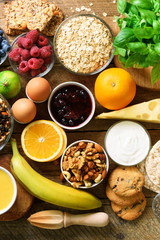 Healthy breakfast ingredients, food frame. Granola, egg, nuts, fruits, berries, toast, milk, yogurt, orange juice, cheese, banana, apple on wooden rustic background, top view, copy space.