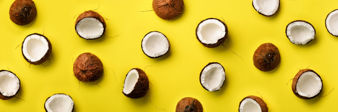 Pattern with ripe coconuts on yellow background. Top View. Copy Space. Pop art design, creative summer concept. Half of coconut in minimal flat lay style.