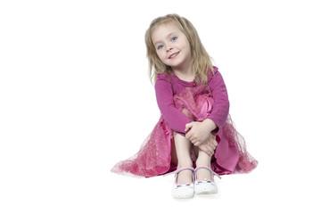 Portrait of little girl sitting on floor, hugging her knees, isolated on white background