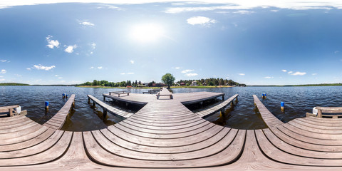 full seamless panorama 360 by 180 angle view wooden pier for ships on huge forest lake in sunny summer day in equirectangular projection, skybox VR content. Wind of freedom