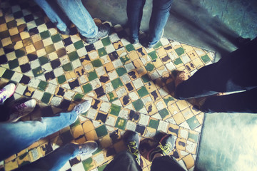 Group of people standing on tiled floor, top view on legs