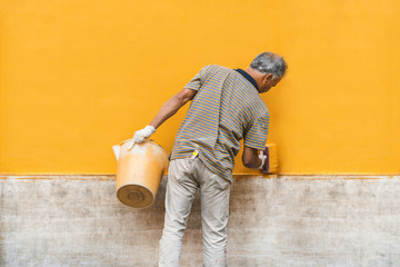 The painter with a bucket paints the facade of the building in yellow color Fototapete