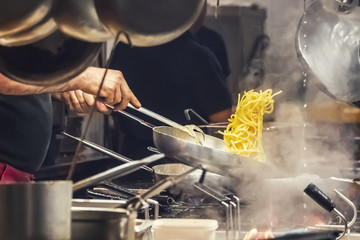 The cook prepares pasta in a restaurant