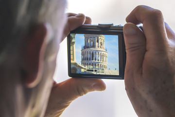 A man is making a photo of the Tower of Pisa