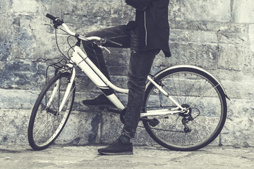 A man on a bicycle standing near a wall. Toned
