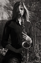 Attractive young woman with saxophone. Black and white photography