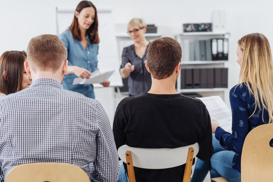 Women lecturing to students or business colleagues