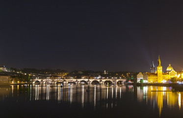 View of the famous Charles Bridge illuminated at night. Charles Bridge is a historic gothic-style stone bridge that crosses the Vltava river in Prague connecting the Old Town to the Lesser Quarter