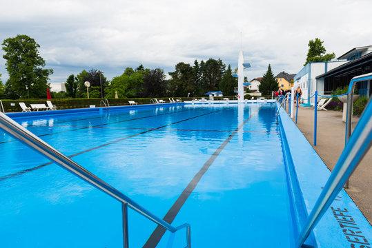Blick über ein Schwimmbecken eines Freibades mit ruhigem Wasser vor der Öffnungszeit