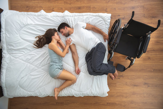 The woman and a disabled man laying on the bed. view from above