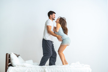 The man and a woman jumping on the bed