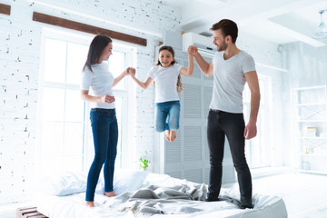 The girl jumping with parents on the bed