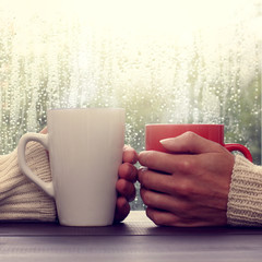 warming relations after rain/ red and white mug of hot drink in the hands of a couple, when the sun comes out