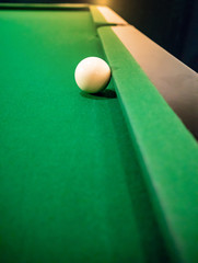 Cue ball on cushion on green snooker table.