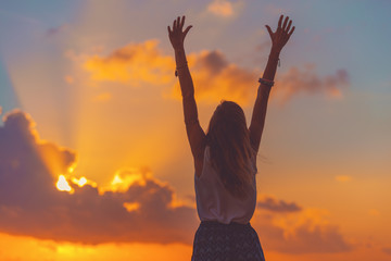 Girl with arms wide open enjoying sea / ocean scenery in sunset.