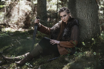 Viking woman with sword wearing traditional warrior clothes in a deep mysterious forest.