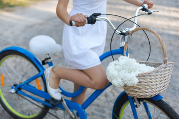 beautiful girl with a bike. woman with a woman's bike and a basket of flowers. girl with a lady's bike.