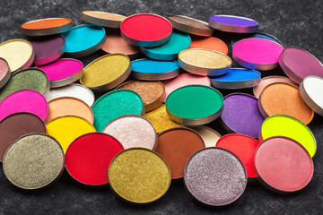 big amount of shimmer and matt multicolored circle shaped eye shadows lying on a black background. concept of healthy make up products