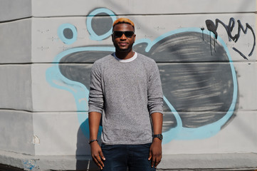 Stylish african american boy on gray sweater and black sunglasses posed at street. Fashionable black guy against graffity wall.